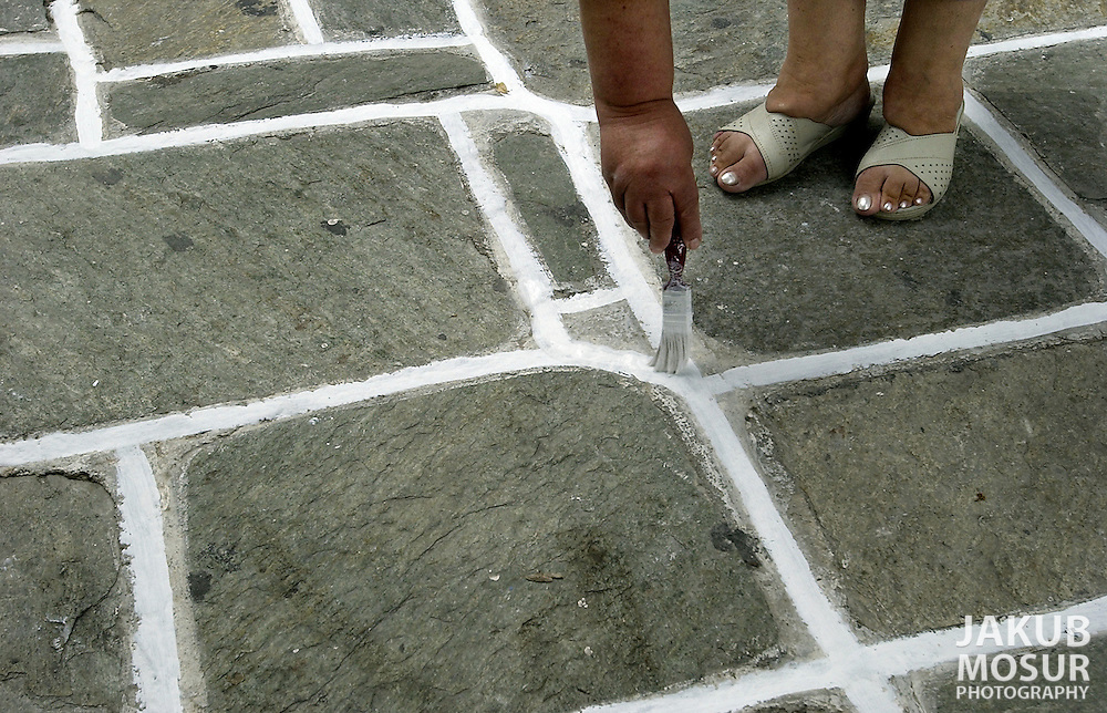 A woman paints the grout around stones with white paint in the town of Ios on the island of Ios, Greece on October 12, 2002 after a night of election parties. Photo by Jakub Mosur