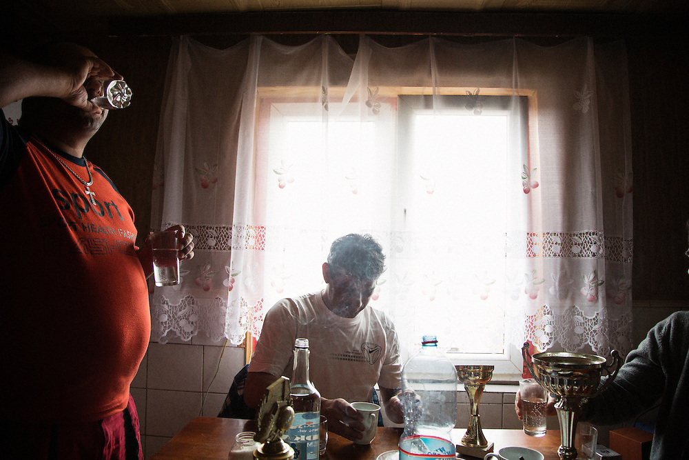 Men drink vodka in the Roma settlement in Ostrovany, Slovakia.