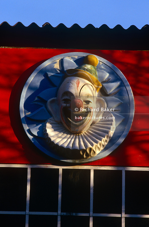 An original clown face feature still adorning the wall of an old building at the regenerated Butlins holiday centre at Minehead.