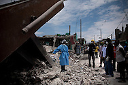 Forestein Claude, left, a Cash-for-Work laborer, talks to his colleagues in front of a home where they found the remains of a woman in the debris, in the Fort National neighborhood of Port-au-Prince, Haiti, Thursday, April 1, 2010.  Many Haitians are working in the UN-sponsored Cash-for-Work program in which they make about $4 a day to clear rubble.