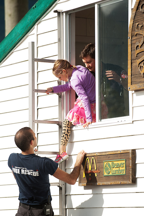 Squamish Firefighter Brandon Biln helps local kids escape from the fire safety house.<br /> <br /> Squamish Fire Rescue open house.  Sunday, October 5th, 2014.<br /> <br /> Photo Credit: David Buzzard
