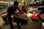 "A family just arrived from Chennai (India) drags heavy suitcases from the carousel in the arrivals of Heathrow Airport's Terminal 5. 50-70,000 pieces of British Airways baggage a day travel through 11 miles of conveyor belts which were installed in a 5-storey underground hall beneath the 400m (a quarter of a mile) length of Terminal 5. T5 alone has the capacity to serve around 30 million passengers a year and was completed in 2008 at a cost of £4.3bn. The system was designed by an integrated team from the airport operator BAA, BA and Vanderlande Industries of the Netherlands, and handles both intra-terminal and inter-terminal luggage. From writer Alain de Botton's book project ""A Week at the Airport: A Heathrow Diary"" (2009)."