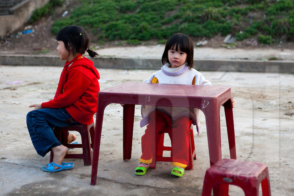 Color film portrait of two girls sitting on red plastic stools, one of whom looks to the camera with a sad expression, Hanoi, Vietnam, Southeast Asia