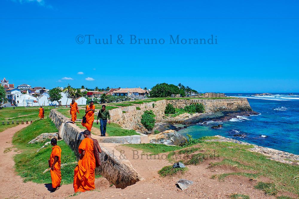 Sri Lanka, province du sud, district de Galle, Galle, Vieille ville classée patrimoine mondial de l'UNESCO, moines marchant sur les remparts du fort // Sri Lanka, Southern Province, South Coast beach, Galle, old town, Dutch fort, UNESCO World Heritage site, Lighthouse and buddhist monks on the rampart