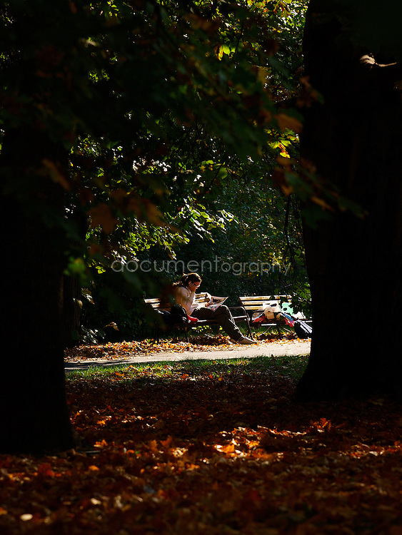 A woman reads a magazine on a bench in Margaret Island Park, Budapest, Hungary.