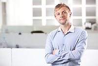 Portrait of young businessman with arms crossed standing at office