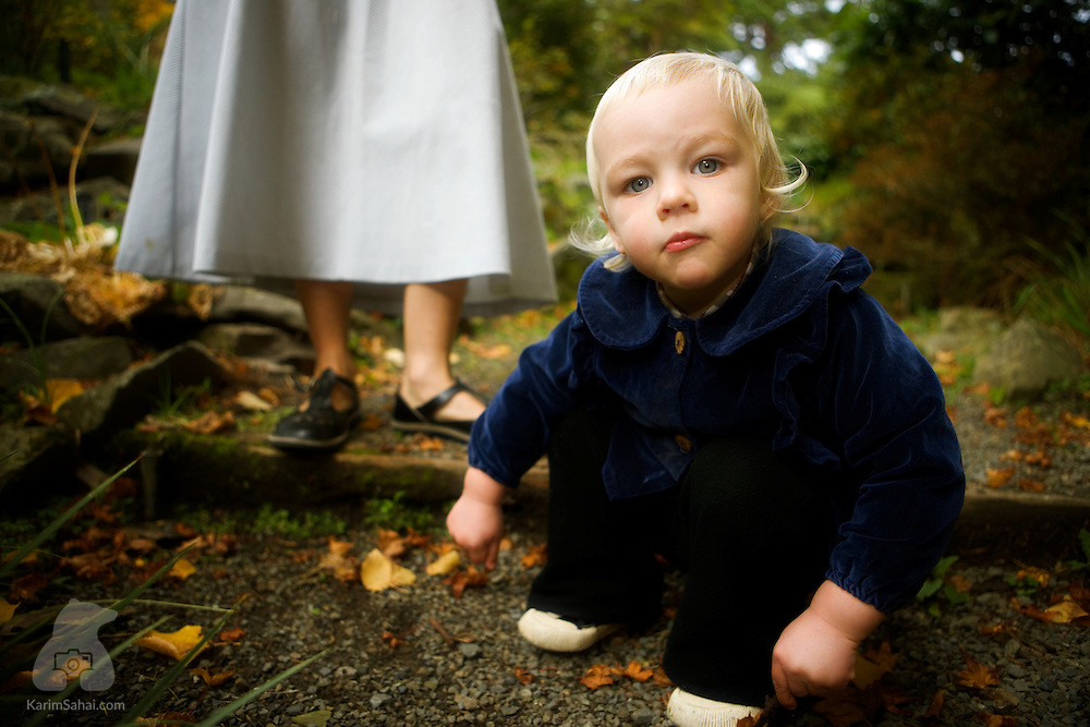 A small boy sitting on the ground looks curiously towards the camera while his mother stands in the background.