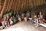 Batwa members act out a story in the village house of Mukuno, Uganda, they are a group of Batwa pygmies from the Bwindi Impenetrable Forest in Uganda. They were indigenous forest nomads before they were evicted from the Bwindi Impenetrable Forest when it was made a World Heritage site to protect the mountain gorillas. The Batwa Development Program now supports them.