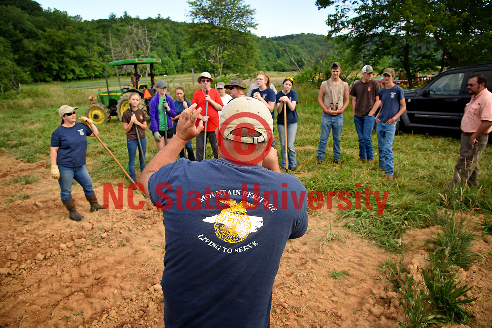 Yancey County cooperative extension agriculture technician Adam McCurry gives direction on planting to FFA students.