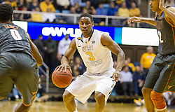 West Virginia Mountaineers guard Juwan Staten (3) looks to drive between defenders against the Texas Longhorns during the first half at the WVU Coliseum.
