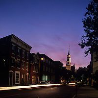 USA. Maryland, Twilight lights sky behind church steeples in downtown Frederick by blurred car lights