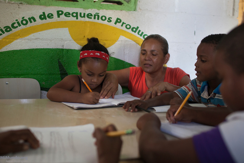 "Georgina Oseres (right), director of the Sala de Tarea, or Homework Center, Niños del Puente de Mao, helps out Adrii Ventura, 5, whose father is Luis Alfredo Ventura, a worker for small producers of La Santa Cruz. Sponsored by Fairtrade via La Santa Cruz, the Sala de Tarea was inaugurated in 2010. Oseres explains: ""The center was born in 2010 out of need. Roughly 80% of the residents of el Puente de Mao are workers for La Santa Cruz banana producers, and so we needed to find activities for the kids after school. We have received some money from [the] Fairtrade [premium] for the construction of a roof here, as well as to upkeep this small center and for supplies for the 25 students, all between 6 and 11 years of age. The idea is to help them with their homework if their parents are busy working."" La Santa Cruz is an association of small producers in northern Dominican Republic that exports organic bananas certified by the Fairtrade Labelling Organization (FLO). As of December 2014, La Santa Cruz exports 100% of its total production via FLO to England, Germany, France and the Netherlands. Once La Santa Cruz finishes processing its organic certification, it hopes to export 100% of its production as organic bananas via FLO. Mao, Valverde, Dominican Republic. December 8, 2014."