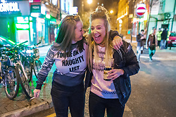 """© Licensed to London News Pictures . 15/12/2017. Manchester, UK. A woman wearing a Christmas jumper that reads """" You're on my naughty list """" walks with a friend through Manchester's """" Gay Village """" . Revellers out in Manchester City Centre overnight during """" Mad Friday """" , named for historically being one of the busiest nights of the year for the emergency services in the UK . Photo credit: Joel Goodman/LNP"""