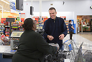 Nick Rhoades talks with a cashier as he buys snacks for a PITCH meeting at Walmart in Waterloo, Iowa on Thursday, November 7, 2013.