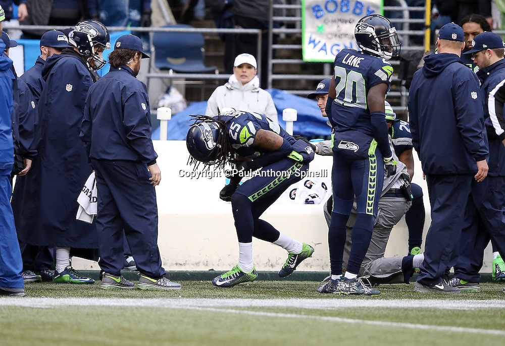 Seattle Seahawks cornerback Richard Sherman (25) bends over and holds his injured arm after a fourth quarter play during the NFL week 20 NFC Championship football game against the Green Bay Packers on Sunday, Jan. 18, 2015 in Seattle. The Seahawks won the game 28-22 in overtime. ©Paul Anthony Spinelli