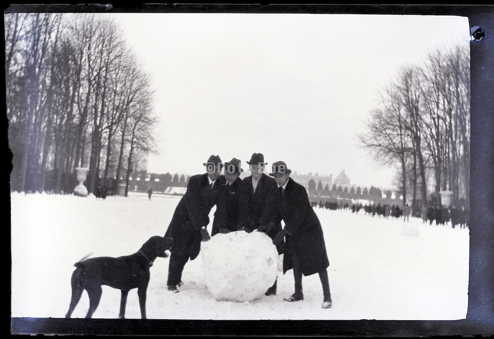 male friends making a big snowball Paris early 1900s