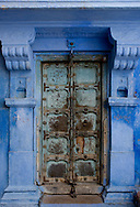 An old metal door at a traditional blue painted house in Jodhpur, Rajasthan, India
