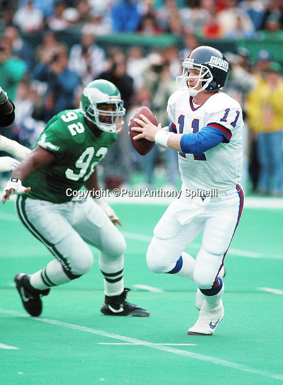 New York Giants quarterback Phil Simms (11) looks to pass while being chased by Philadelphia Eagles defensive end Reggie White (92) during the NFL football game against the Philadelphia Eagles on Nov. 25, 1990 in Philadelphia. The Eagles won the game 31-13. (©Paul Anthony Spinelli)