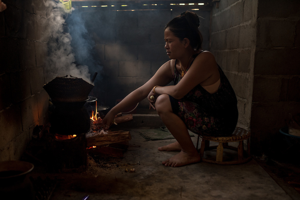 A woman tends to her cooking fire in the village of Khoc Kham. The village is not connected to the main electrical grid and many residents operate their own turbines to power lights and sometimes small appliances.