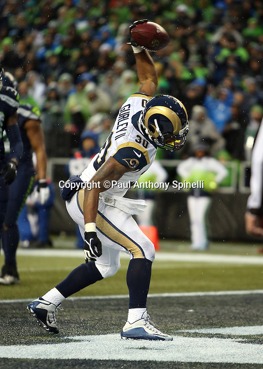 St. Louis Rams running back Todd Gurley (30) spikes the ball in celebration after running for a 2 yard touchdown that gives the Rams a 23-10 fourth quarter lead during the 2015 NFL week 16 regular season football game against the Seattle Seahawks on Sunday, Dec. 27, 2015 in Seattle. The Rams won the game 23-17. (©Paul Anthony Spinelli)