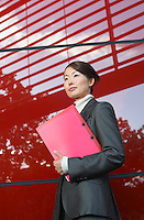 Businesswoman holding notebook Standing Beside red Building