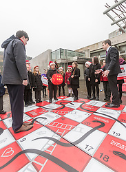 "Campaigners from Shelter Scotland raise awareness of their campaign ""Homelessness - Far From Fixed"" outside the Scottish Parliament in Edinburgh. They are joined by carol singers from Corstorphine Primary School, a Christmas tree and a giant snakes and ladders board game - Chance Not Choice - which illustrates how life chances affect people's ability to keep a roof over their head.<br /> <br /> Pictured: Daniel Johnson from Scottish Labour playing Chance Not Choice with Evan Jones from Costorphine Primary School throwing the dice"