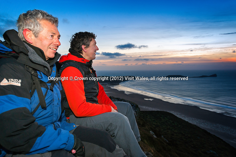 Two male walkers on Rhossili Down at sunset with Worm's Head in background<br /> Gower<br /> Swansea County<br /> South<br /> Walking<br /> Activities and Sports