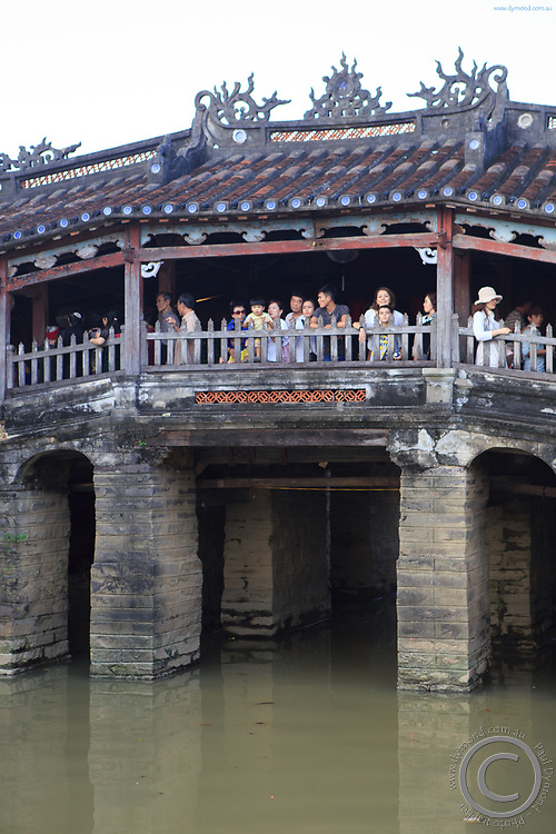 Tourists pose for photos on the Japanese Covered Bridge in Hoi An, Vietnam