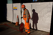 Construction site Banksman waits to control local traffic where a concrete truck is due to emerge in Soho, central London.