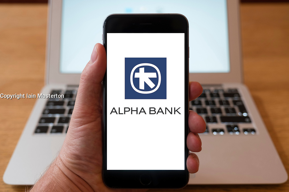 Using iPhone smartphone to display logo of Alpha Bank, a large Greek bank.