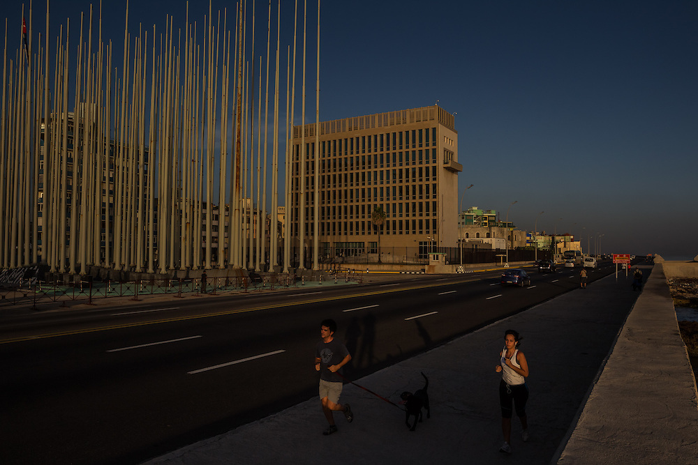 HAVANA, CUBA - JULY 20, 2015: Runners pass by the U.S. embassy on Monday morning. After more than half a century defined by mistrust and rancor, the United States officially reopened its six-story embassy in Havana today, marking a watershed moment of transition for the two countries as they lean toward closer diplomatic ties and ease past one of the last remnants of the Cold War.  President Barack Obama, when announcing an end to the diplomatic freeze, eased travel restrictions, opened the door for more remittances to Cuba and expanded the amount of goods that visiting Americans could bring back home – like Cuban cigars and rum. He even removed the country from the list of nations that sponsor terrorism. President Raul Castro, meanwhile, has spent the last five years, before the thaw even began with the Obama administration, attempting to alter his nation's economic dysfunction, ordering the firing of government employees, encouraging a slow but fresh influx of Cubans into self-employment and even creating a special economic zone in the coastal city of Mariel to attract foreign investment.  PHOTO: Meridith Kohut for The New York Times