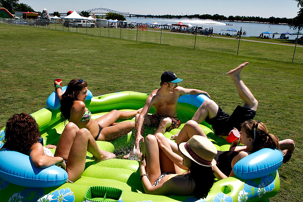 Matt Griffin of Seattle backflips out of the a party island shared with, clockwise from right, Rachael Hiatt, Dana Werner, Natalie Corcimiglia, Alisha Martin and Max Hubbard at Greg and Jan Bowers' Pasco home as an unlimited heat runs on the river in 2010. The group are former college friends with their son, Scotty Bowers, a Southridge High School graduate and got to enjoy some of the best seats in the house.