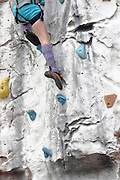 Young teen girl climbs up an artificial climbing wall close up of the feet and special climbing shoes