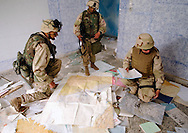 U.S. Air Force Col. Greg Cook, right, from the Global Airfield Assessment Team, searches through maps and papers left behind in a headquarters building at an Iraqi Helicopter/Air Base on the outskirts of Karkuck. Helping him are Army Staff Sgt. Samuel Hall, left, and Sgt Furman Campbell, middle, both from the 173rd, 1st of the 508, who gave the GAAT added security as they convoyed from Kirkuk Air Base to K-1, another Iraqi military airfield on the outskirts of Kirkuk.  (Alan Lessig/Air Force Times)