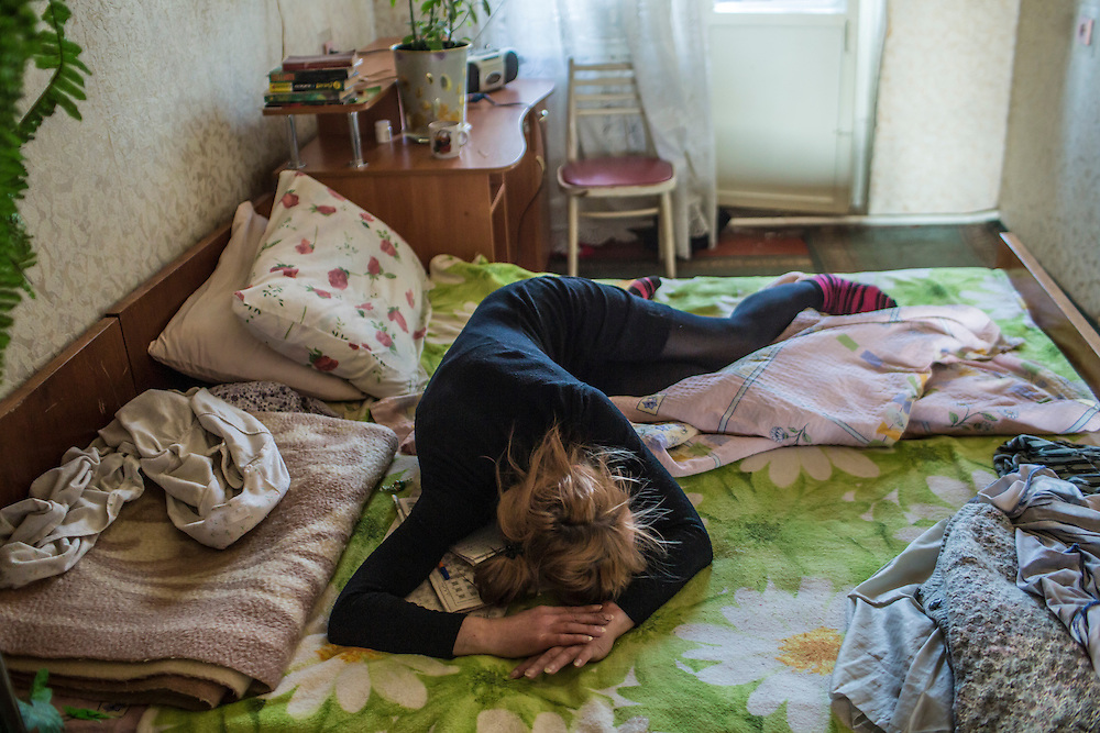 Olga demonstrates how she hid when on January 24 shelling hit her neighborhood of Vostochniy on Monday, March 9, 2015 in Mariupol, Ukraine.