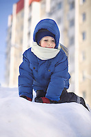 Young boy climbing in the snow