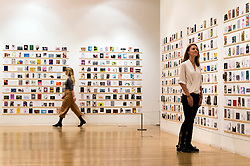 © Licensed to London News Pictures. 08/04/2016. Two members of staff view The Royal College of Arts(RCA) 22nd annual Stewarts Law RCA Secret exhibition of postcards designed by well-known artists and designers. London, UK. Photo credit: Ray Tang/LNP