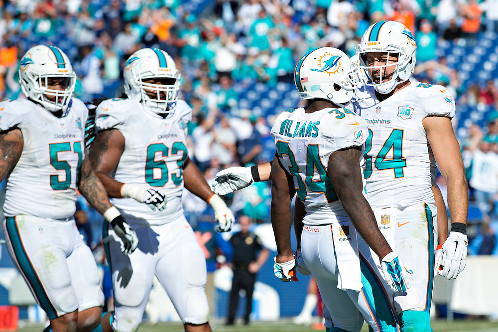 NASHVILLE, TN - OCTOBER 18:  Jordan Cameron #84 celebrates after scoring a touchdown with Damien Williams #34 of the Miami Dolphins during a game against the Tennessee Titans at LP Field on October 18, 2015 in Nashville, Tennessee.  The Dolphins defeated the Titans 38-10.  (Photo by Wesley Hitt/Getty Images) *** Local Caption *** Jordan Cameron; Damien Williams