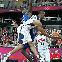 29 July 2012: USA Russel Westbrook passes the ball around Florent Pietrus of France during a 98-71 Team USA victory over Team France, during the men's basketball preliminary, at the Basketball Arena, in London, Great Britain.
