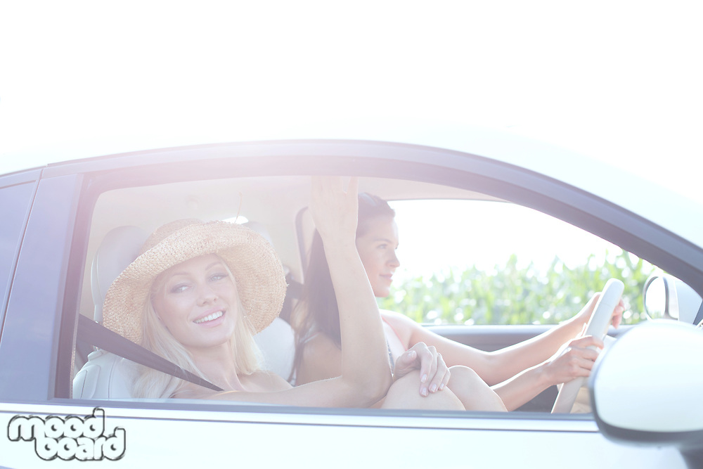 Happy women enjoying road trip on sunny day
