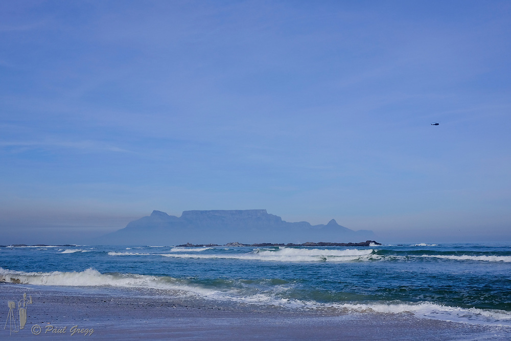 Table Mountain,Cape Town, South Africa. Mussel and other shells litter the beach after heavy seas. A blanket of smog covers the base of Table Mountain in the early winter morning. An old American Huey flies overhead.