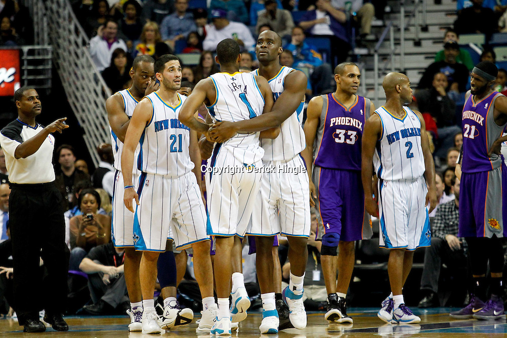 December 30, 2011; New Orleans, LA, USA; New Orleans Hornets small forward Trevor Ariza (1) is held back by teammate center Emeka Okafor (50) following an altercation with Phoenix Suns center Robin Lopez (15) during the second half of a game at the New Orleans Arena. The Suns defeated the Hornets 93-78.   Mandatory Credit: Derick E. Hingle-US PRESSWIRE