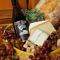 Cork basket with bread, cheese, grapes and wine.