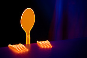 Two glowing forks and a spoon look over a table. Black light Photography.