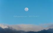 Full moon rises above dark clouds.