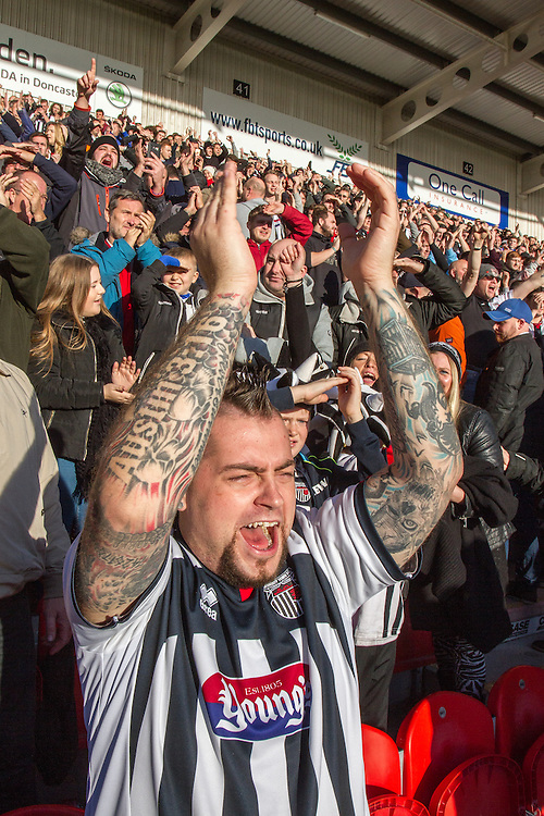 Grimsby Town football club fans in the Doncaster stadium, England, UK