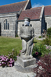 Covid 19 - mask placed on statue of a stonemason in St Georges' churchyard, Langton Matravers, Dorset during Coronavirus lockdown. UK April 2020