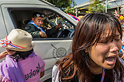 22 DECEMBER 2013 - BANGKOK, THAILAND: An anti-government protestor screams as Thai riot police try to drive to the home of Prime Minister Yingluck Shinawatra. The crowd blocked the police from getting to the home. Hundreds of thousands of Thais gathered in Bangkok Sunday in a series of protests against the caretaker government of Yingluck Shinawatra. The protests are a continuation of protests that started in early November and have caused the dissolution of the Pheu Thai led government of Yingluck Shinawatra. Protestors congregated at home of Yingluck and launched a series of motorcades that effectively gridlocked the city. Yingluck was not home when protestors picketed her home.     PHOTO BY JACK KURTZ