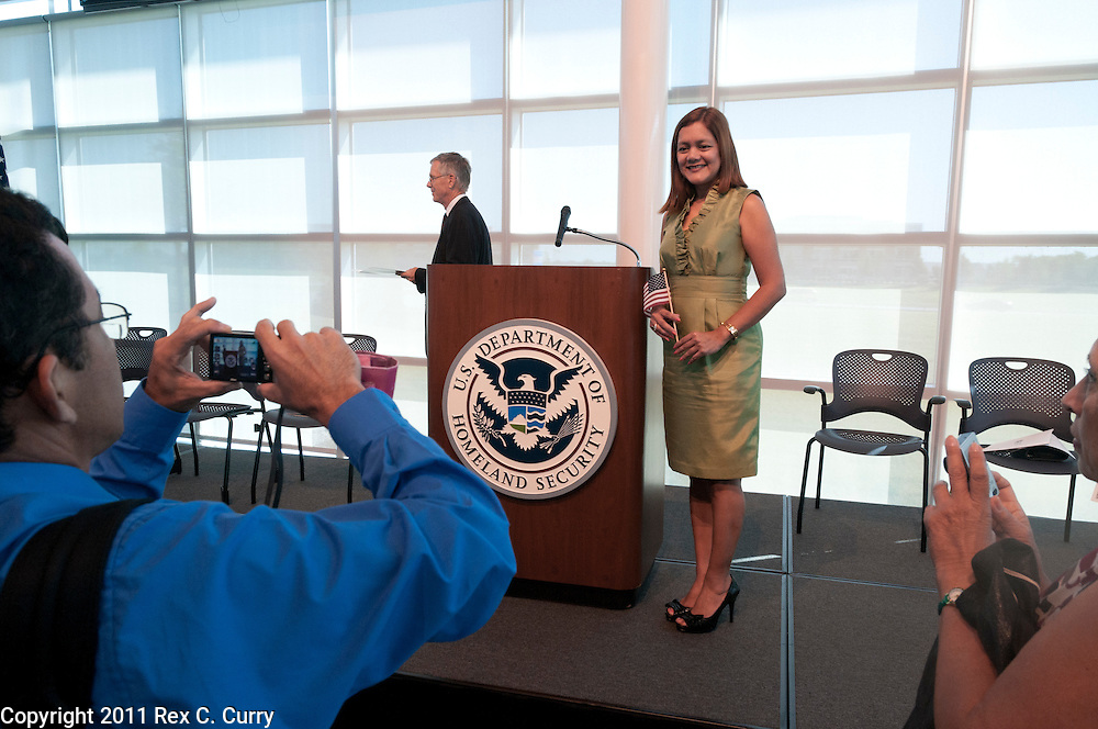 Carla Villacis, from Ecuador poses next to the emblem of the U.S. Department of Homeland Security after a naturalization ceremony at the USCIS office in Irving on June 30, 2011.