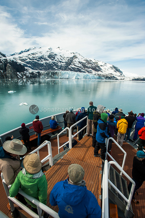 Passengers on the deck of a cruise ship in front of a glacier.